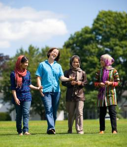 The Basij-Rasikh sisters, on the grounds of the Brooks School with English teacher Leigh Perkins (second from left). From left: Shabana, Shugufa, and Marjeela.