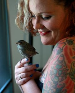 Jodi Swenson holds one the catbirds she is rehabilitating at her home before she releases it back into the wild.