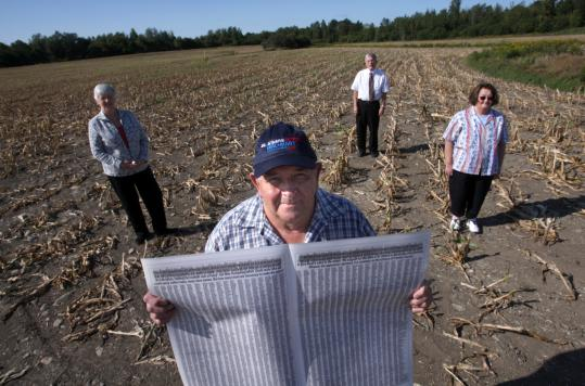 Wal-Mart supporters include (from left) Mary Groff, Raymond Gadue, Bill Groff, and Eileen Gadue at the proposed site in a cornfield. Raymond Gadue held a paper with more than 14,000 signatures of others who back the move.