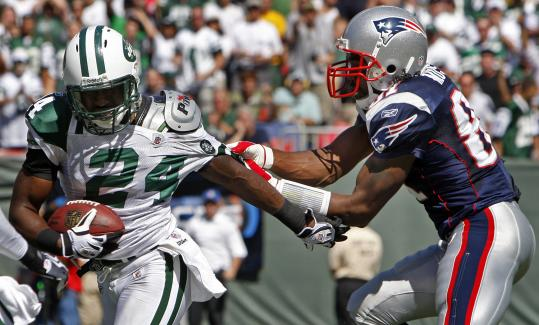 New England's Randy Moss had to switch from receiver to defender after Jets cornerback Darrelle Revis picked off a deep pass intended for Moss in the first quarter. The New York defense had Moss covered most of the game, holding the Patriots star four catches for 24 yards.