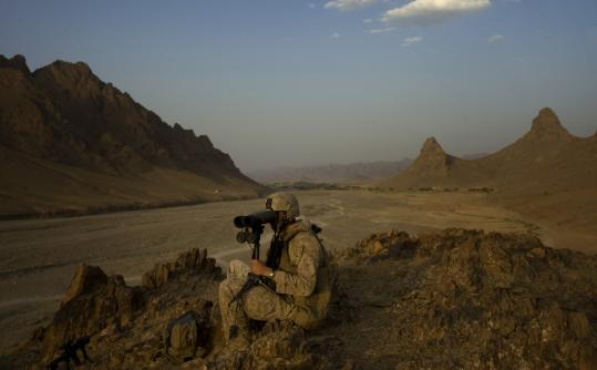 A Marine kept watch in Helmand Province in Afghanistan yesterday. Two officials said the White House is considering expanding operations in Pakistan to refocus on eliminating Al Qaeda.