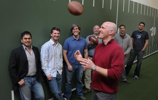 Jeffrey Anderson (center), the CEO and founder of Quick Hit Inc., with the software development team at their Foxborough offices.