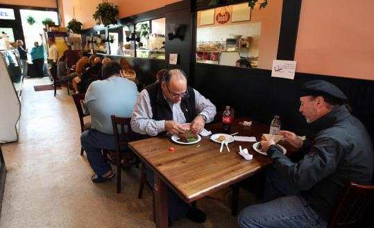 Scott Levine and Bob Cavicchi enjoy a meal at Brookline's Michael's Deli, where diners are asked not to linger over a laptop or read at all.