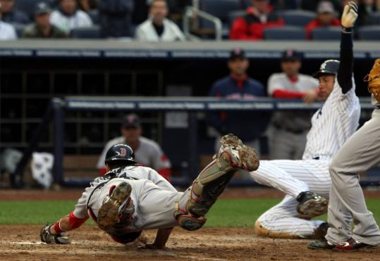 Victor Martinez outraces Derek Jeter to the plate for a force that helped prevent a Yankee rally.