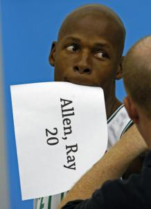 Ray Allen, adjusting his uniform for a photo, holds a paper ID in his mouth.
