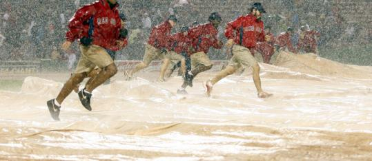 The grounds crew races to put down the tarp as the skies open up with a deluge of rain.