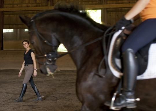 Jane Karol, a psychotherapist and top-level dressage competitor, scrutinizes a rider's form during a dressage training session at her farm in Concord.