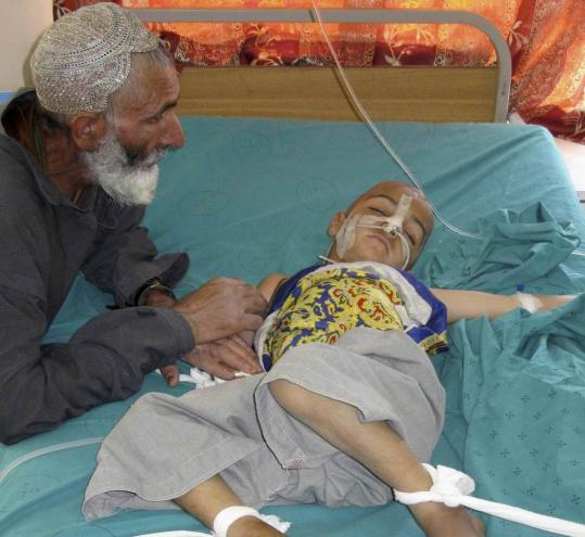 A wounded Afghan boy lay in a hospital yesterday in Kandahar, where a passenger bus struck a roadside bomb. The attack underscored the growing danger of road travel for civilians.