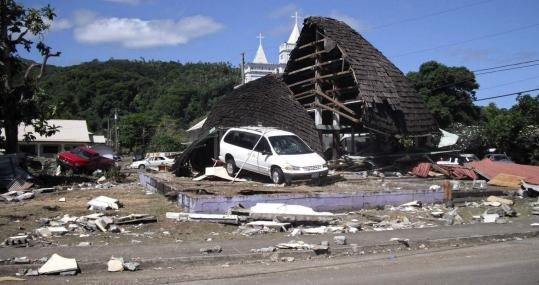 A church lay in ruins yesterday after a series of tsunami waves struck American Samoa, reaching up to a mile inland.