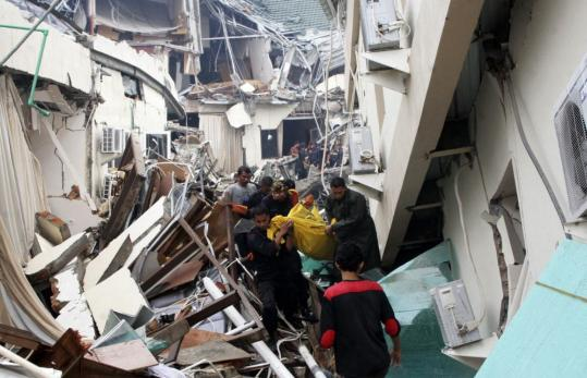 Soldiers and volunteers carried a survivor from the wreckage of a collapsed hotel in Padang, on Indonesia's Sumatra Island, yesterday. Officials said the death toll is expected to rise as rescue efforts continue.