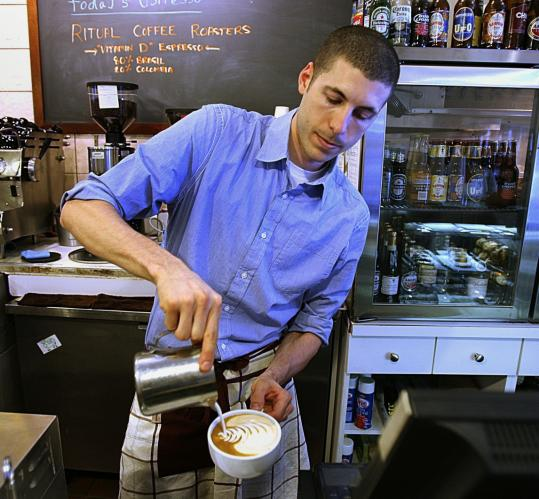At Taste Coffee House, Nikolas Krankl pours a latte, complete with a design in the foam. Krankl, 25, bought the coffee shop in March 2008, renamed it, and invested in high-end equipment.