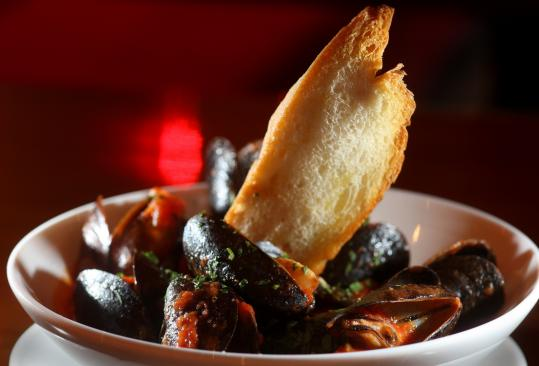 The mussels fra diavolo, served with a single piece of garlic toast, are plump, tender, and briny in a spicy tomato broth.