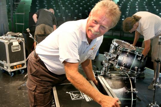 Andy Bergsten sets up equipment at the South Shore Music Circus for a B.B. King show. Bergsten's company rents instruments and more to players.