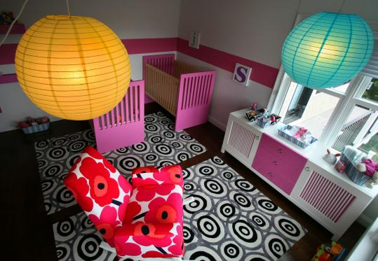 Cheryl Kaufman's 15-month-old twins, Sydni and Jaedyn, share a bedroom in Cohasset outfitted with simple furniture, bold, geometric shapes, and bright colors.