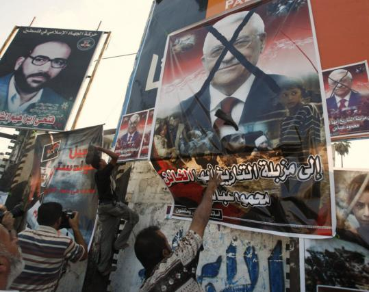 Demonstrators in Gaza threw shoes at a poster of Mahmoud Abbas yesterday, protesting the Palestinian president's request that the UN suspend action on a report detailing war crimes.