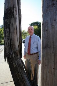Lowell Mayor Bud Caulfield stands next to what he calls the most dangerous double pole in the city.
