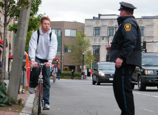 At Harvard and Beacon streets in Brookline, traffic officer Kevin Sullivan warns Ryan Devereaux against ignoring traffic rules.