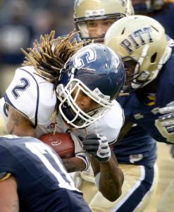 UConn's Andre Dixon attracted a crowd on this run, but finished with 95 yards and a TD in a loss to Pittsburgh.