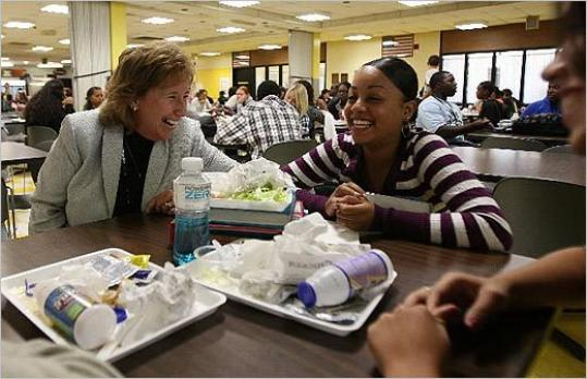 Principal Susan Szachowicz, shown chatting at lunch with Yiriam Lopez, is in many ways the school's biggest cheerleader.