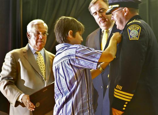 As Mayor Thomas M.Menino and Police Commissioner Edward F. Davis looked on, Michael Perkins, 13, pinned a badge on his father, Deputy Superintendent Earl O. Perkins, during a promotional ceremony in 2007.