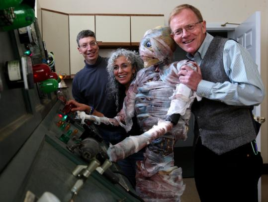 The Rev. John Gibbons checks one of the Halloween creatures at the First Parish in Bedford's haunted house, backed up by Gene Kalb and Lisa Rubin.