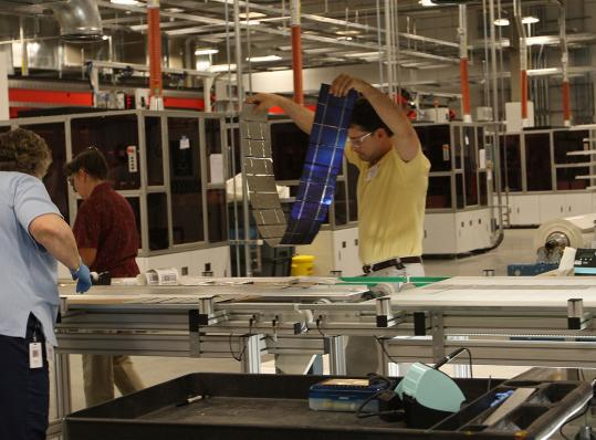 Workers at Evergreen Solar Inc. put together solar panels at its new Devens manufacturing plant.