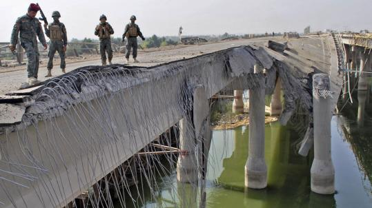 Iraqi Army soldiers inspected a bridge destroyed yesterday in a truck bomb attack in Ramadi. The bridge is on a highway used by the US military to transport equipment out of the country.