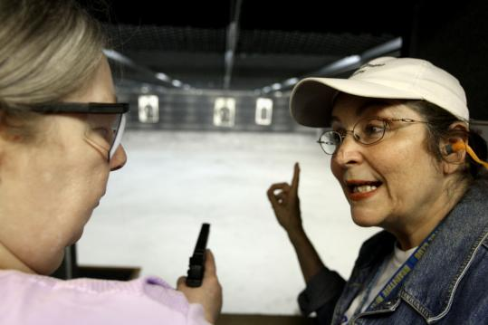 Linda Tague (left) gets instruction from Lynn Roberts at the Braintree Rifle & Pistol Club, which plays host monthly to the Second Amendment Sisters, a national organization that advocates firearms safety for women.