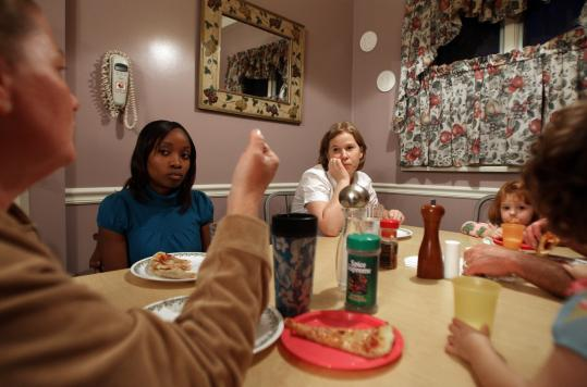 Pam Richardson (wearing white blouse at table), a teacher at Lee Academy Pilot School in Dorchester, and teacher assistant Misheka Barrosy (to her right) paid a home visit and shared a pizza with the Coyne family.