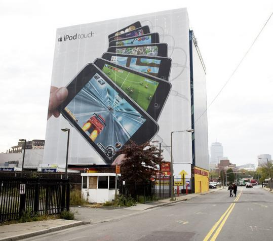 An ad for the Apple iPod Touch is displayed on the side of a Planet Self Storage site in Boston.