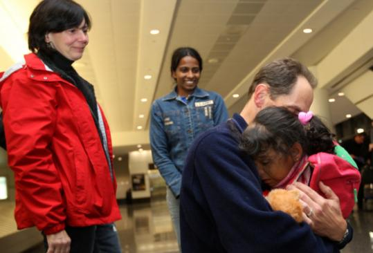 Liz Smith watched as her husband, Evan Katz, embraced Hasi upon her arrival with her guardian, Ruveni Balasooriya.