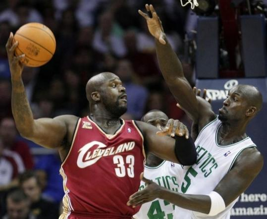 New Cavaliers big man Shaquille O'Neal (33) tries to pass around Kevin Garnett in the first quarter.