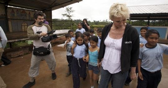Rainforest Foundation cofounder Trudie Styler joins children as she delivers a water purification system to their school, filmed by documentary maker Joe Berlinger (left). Plaintiffs' attorney Steven Donziger (below left) and Styler in the Ecuadoran Amazon, with Berlinger again filming.