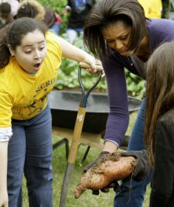 SWEET SURPRISE - A girl from Washington's Bancroft Elementary School was impressed with the sweet potato, held by Michelle Obama, harvested at the White House.
