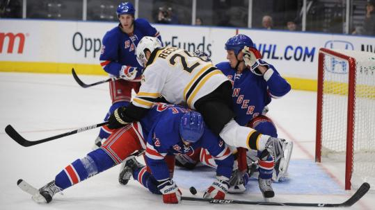 Three Rangers are eyeing the Bruins' Mark Recchi as he fights for the puck in the third period.