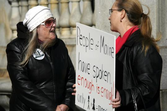 Two people argued their differences regarding same-sex marriage yesterday in front of City Hall in Portland, Maine. Supporters and opponents had to wait until the early morning before it was determined that Maine voters had rejected the marriage law.