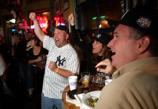 Yankee fans (from left) Steve Macary (wearing team jersey) of Waltham, Linda Borrelli of Boston, and Keith Mayer of Boston, watched the Series game against the Phillies last night.