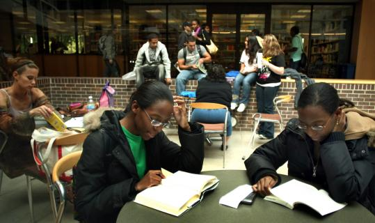 In the atrium lobby of Quincy College, Sabienne Maceus (left) and her twin sister, Sabine, of Mattapan, read their textbooks between classes.