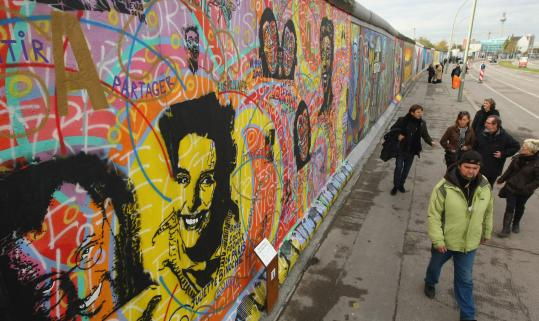 Visitors walked by the restored murals along the former Berlin Wall known as the East Side Gallery on its official re-opening day yesterday. The artists who created the paintings in 1990 repainted their works after the surface of the wall was replaced.