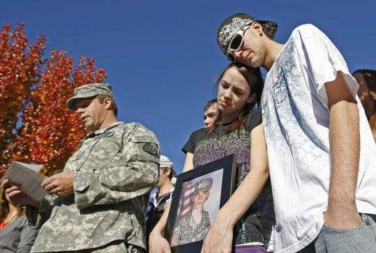 Ashlee Brewer displayed a picture of her brother, Private First Class Aaron Thomas Nemelka, with her husband, Adrian (right), uncle, Major Mike Blades, and other family members in Utah.