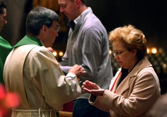 Maria Lobo, of Brazil, received Communion from the Rev. Greg Staab at St. Francis Chapel at the Prudential Center in Boston.