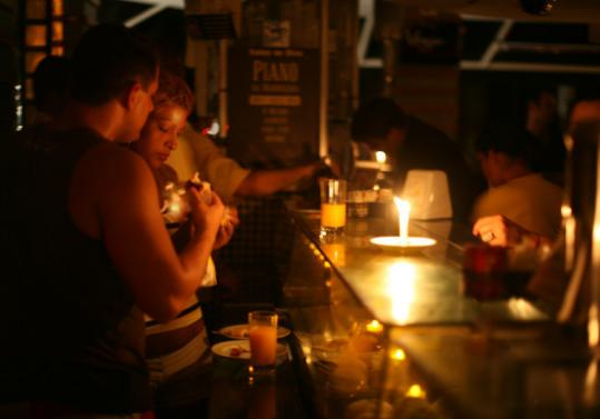 People ate by candlelight at Copacabana Beach in Rio De Janeiro yesterday after storms short-circuited transformers, plunging much of the country into darkness.