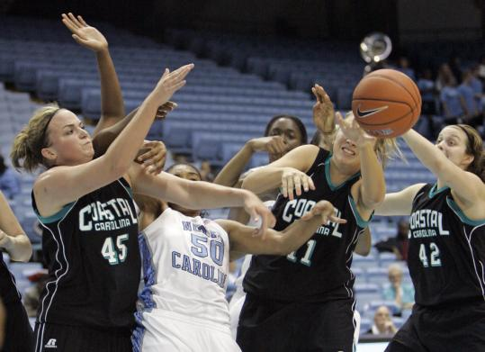 North Carolina's Italee Lucas (50) battles Coastal Carolina's Elizabeth Weaver, Lauren Grochowski, and Taylor Epley during the Tar Heels' win.