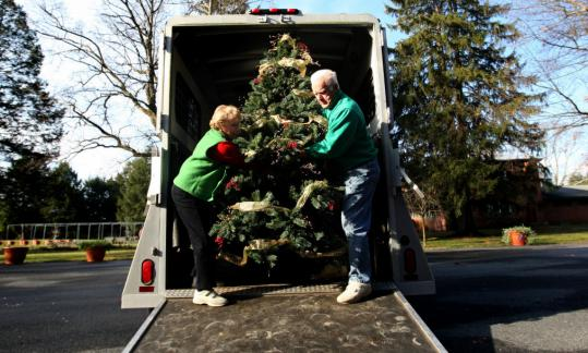 Gloria Freitas-Steidinger and her husband, Paul Steidinger, unload their contribution to the Massachusetts Horticultural Society's Festival of Trees in Wellesley.