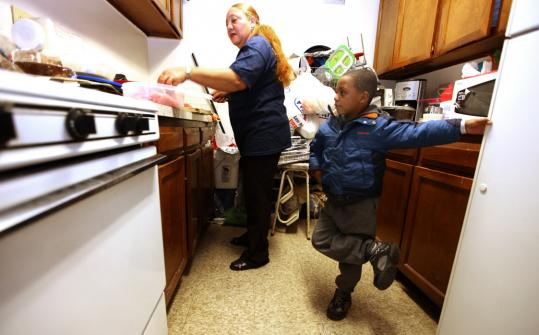 Ysidra Frias, who is having a tough time finding a job, prepared lunch in Lynn on Thursday with her grandson, Felix Rosario. She has found more people than ever in her situation.