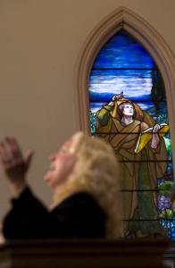 The Rev. Suzanne Andrews, pastor of First Baptist Church in Brattleboro, preached yesterday, with the church's Tiffany stained-glass window visible behind her. The church plans to sell the window to help pay its bills, including for operation of a homeless shelter.