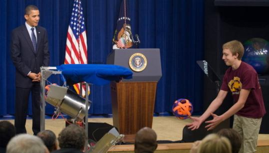 President Obama watched high school student Steven Harris play catch with a robot at a Capitol Hill event on initiatives in science education. Obama plans a national science fair next year.