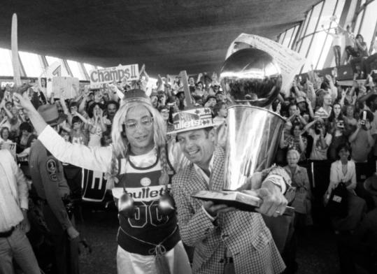 Washington Bullets owner Abe Pollin held up the NBA Championship trophy at Dulles Airport after his team defeated the Seattle SuperSonics in 1978.