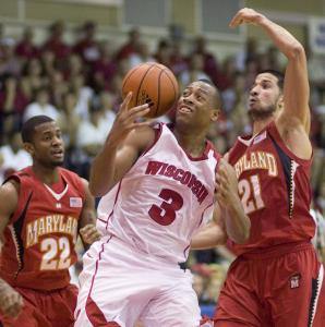 Wisconsin's Trevon Hughes tries to get the handle on a loose ball with Adrian Bowie (22) and Greivis Vasquez defending.