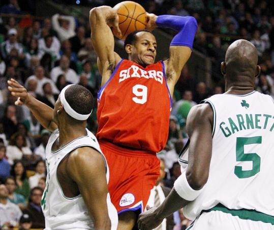 The Sixers' Andre Iguodala looks for an open teammate as Celtics Paul Pierce (left) and Kevin Garnett close in.